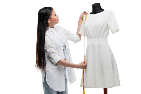 smiling young asian tailor measuring stylish white dress on dummy Stock Photo