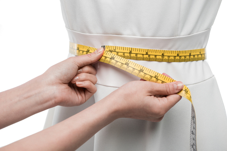 cropped view of dressmaker measuring white dress on dummy, Stock Photo