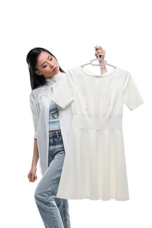 Aziatische meisje houdt hanger met witte jurk, geïsoleerd op wit