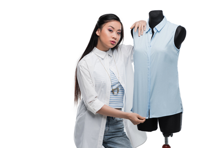 attractive young asian fashion designer posing with blouse on dummy