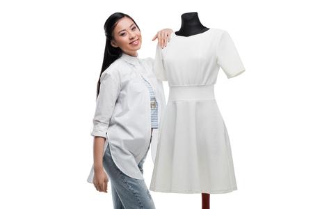 happy asian fashion designer posing with stylish white dress on dummy Stock Photo