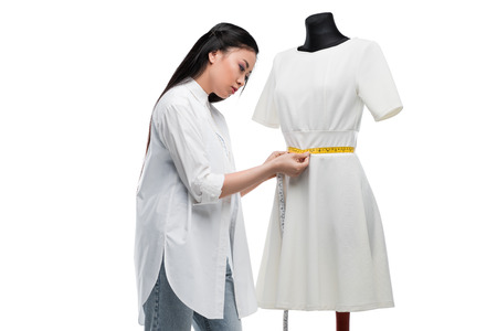 attractive concentrated asian tailor measuring stylish white dress on dummy Stock Photo