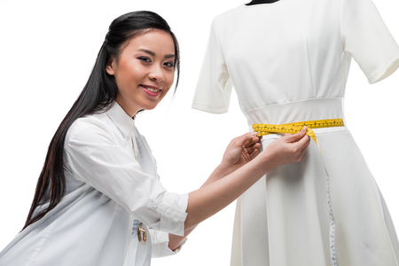beautiful smiling asian fashion designer measuring stylish white dress on dummy