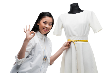 happy young asian dressmaker measuring white dress and showing ok sign Stock Photo