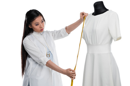 concentrated young asian dressmaker measuring stylish white dress on dummy Stock Photo - 83751521