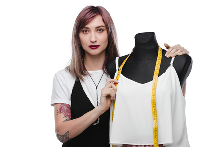 attractive fashion designer with purple hair standing with dummy and measuring tape