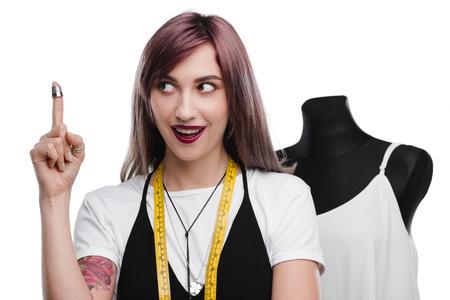schöne aufgeregte Näherin mit Fingerhut zeigen oben Standard-Bild