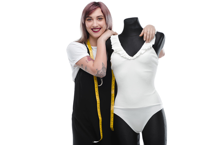 attractive smiling fashion designer with stylish white bodysuit on dummy