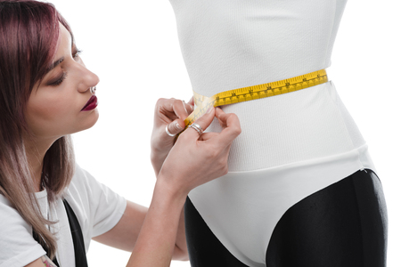 beautiful young seamstress measuring white bodysuit on dummy