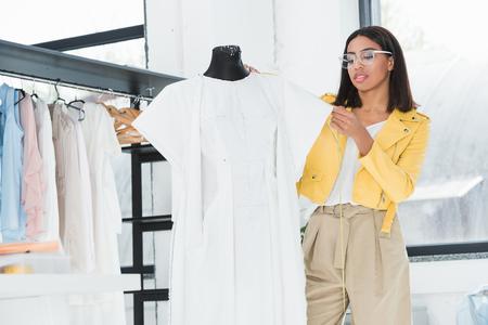 young fashion designer examining white dress on dummy Stock Photo
