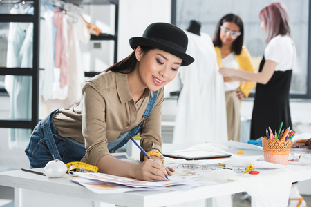 smiling asian fashion designer drawing sketches while colleagues working behind