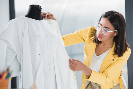 young woman in eyeglasses measuring dummy with tape
