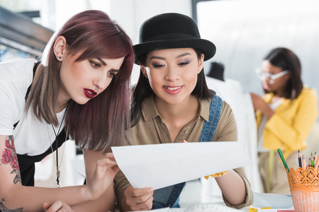 young fashion designers looking at sketch and discussing Stock Photo