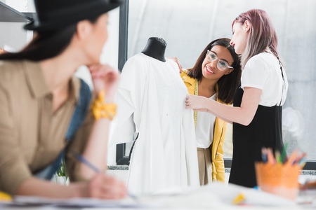 young woman drawing sketch and looking at smiling colleagues working with dress on dummy