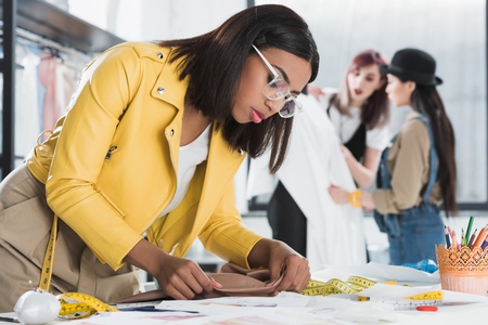 confident fashion designer working with textile at workplace