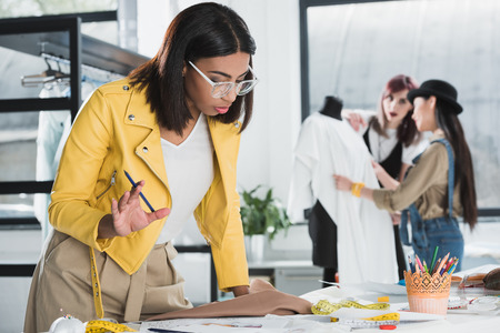 fashion designer looking at sketches on table in workshop Stock Photo