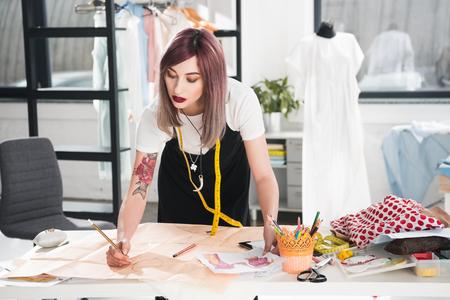 fashion designer working on sketch in clothing design studio