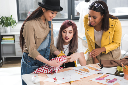 fashion designers together working on project in clothing store