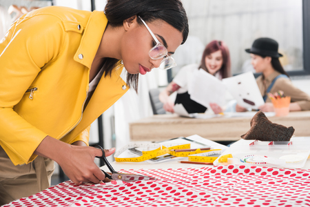 dressmaker in eyeglasses cutting polka dot fabric while her colleagues sitting on background Stock Photo
