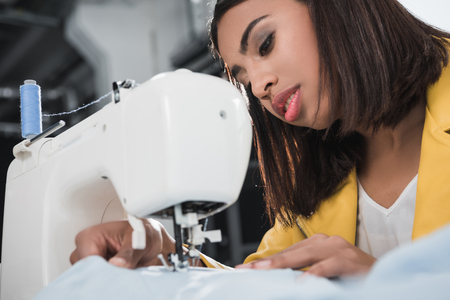 african american seamstress working with sewing machine