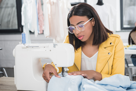 african american seamstress in eyeglasses working with sewing machine Stockfoto