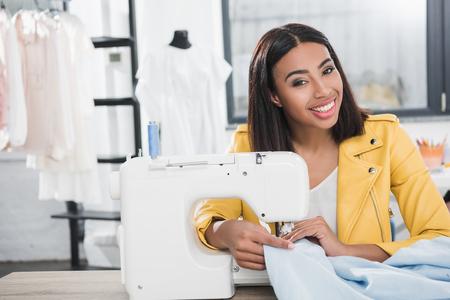 glimlachende naaister camera kijken tijdens het werken met een naaimachine