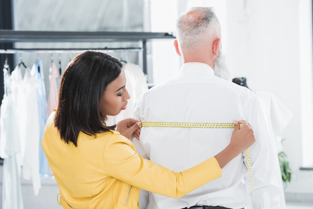 tailored: african american tailor measuring elderly man with tape measure