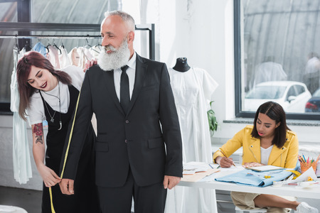 tailored: tailor fitting grey haired man with measuring tape indoors