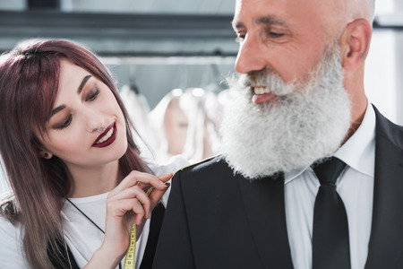 tailored: tailor fitting smiling elderly man for suit jacket indoors Stock Photo