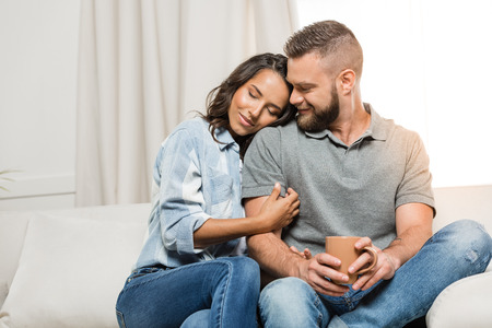 tender couple with closed eyes hugging on sofa at home