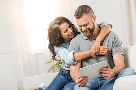 デジタル タブレットを抱いて自宅のソファの上で幸せなカップル