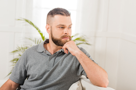 Portrait of pensive bearded man sitting on sofa and looking away