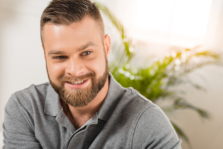 Close-up portrait of handsome bearded man smiling at looking away Foto de archivo