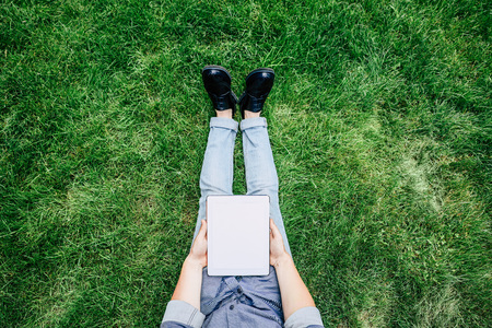 Cropped shot of stylish man using digital tablet with blank screen while sitting on green grass Stock Photo