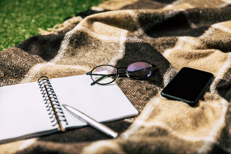 close up view of blank notebook, smartphone and eyeglasses on blanket