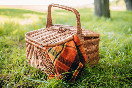 Close-up view of wicker picnic basket with plaid on green grass in park Stock fotó