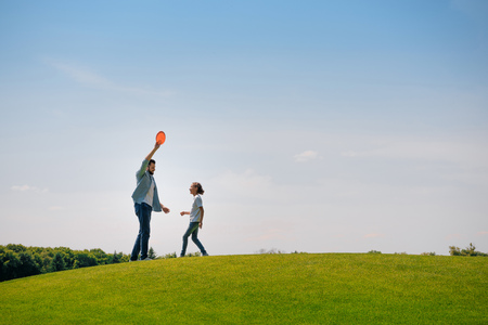 father and daughter playing with flying disk on green lawn Фото со стока