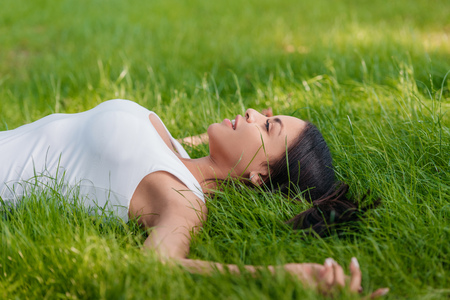 smiling woman lying on green grass with outstretched arms Stock Photo