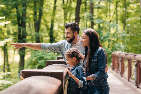 smiling interracial family standing on wooden bridge, while father pointing somewhere into the forest Foto de archivo