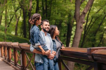 gelukkige interraciale familie die zich op houten brug bevindt, terwijl vader die zijn dochter in wapens houdt