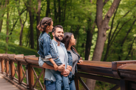happy interracial family standing on wooden bridge, while father holding his daughter in arms
