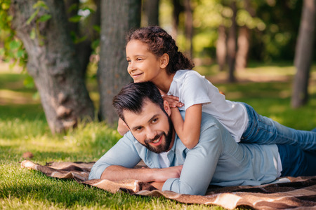 little girl lying on fathers back while spending time together
