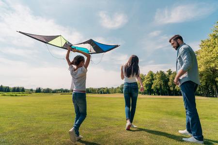 Mädchen hält Drachen mit Eltern zu Fuß in der Nähe in Wiese Standard-Bild - 84052310