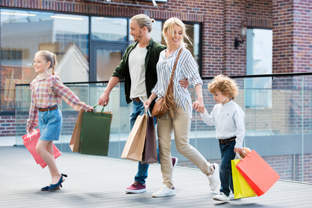 parents and little kids walking with shopping bags Stock Photo