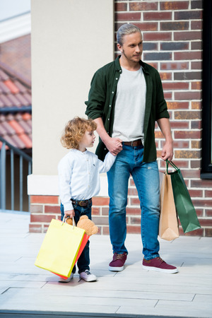 Father and son holding shopping bags while standing