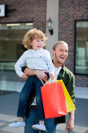 happy father holding little son with shopping bags in hand