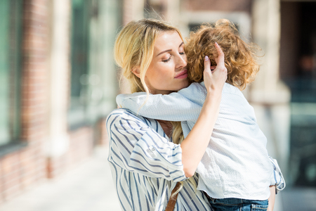 sensual mother with eyes closed hugging little son
