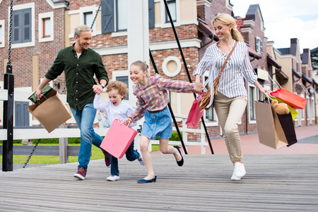 family holding hands and running with shopping bags on the bridge