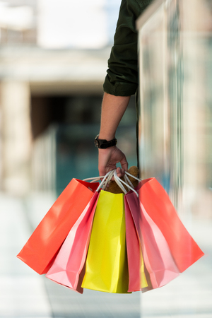 Cropped shot of man holding multicolored paper bags while standing in shopping mall Stock Photo