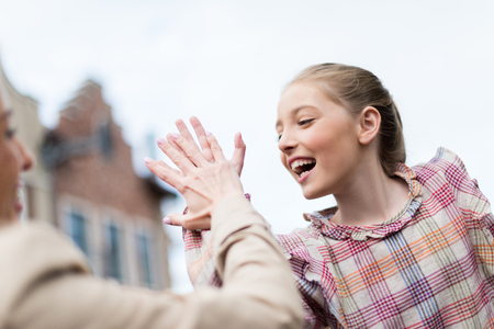 emotional daughter giving high five to her mother